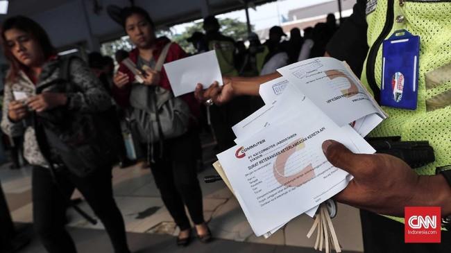 Petugas keamanan membagikan surat keterangan keterlambatan kereta api bagi calon penumpang di Stasiun Bekasi, Jawa Barat, Senin, 23 Juli 2018. (CNNIndonesia/Safir Makki)