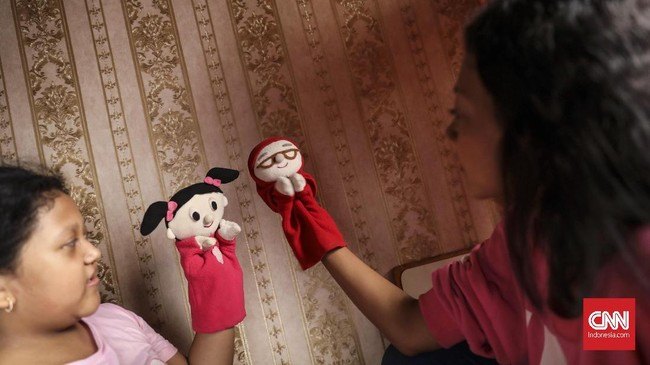 Rara berlatih dengan Sasha memainkan boneka puppet. Bermain layaknya seorang dalang, boneka puppet dimainkan menggunakan tangan dan saling mengborol satu sama lain, mengeluarkan suara dengan bibir yang masih bergerak. (CNN Indonesia/ Hesti Rika)