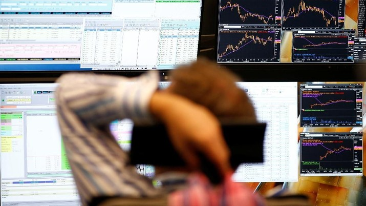FILE PHOTO: A trader sits in front of the computer screens at his desk at the Frankfurt stock exchange, Germany, June 29, 2015.  REUTERS/Ralph Orlowski/File Photo
