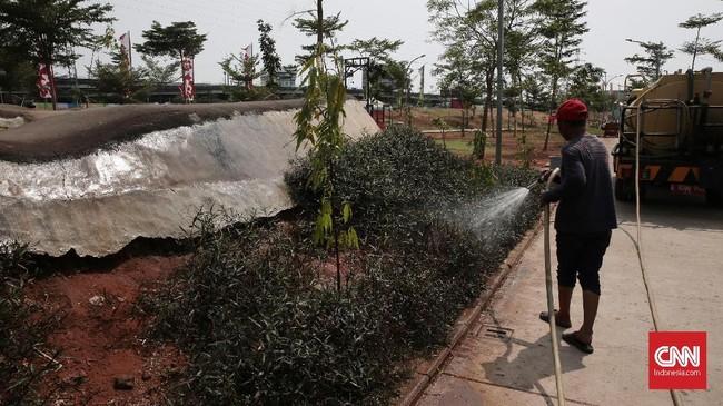 Petugas sedang menyirami taman dan rumput yang masih tumbuh pendek di sekitar arena bermain. Hal lain yang membuat Taman Kalijodo ini kian gersang adalah keberadaan pohon yang belum tumbuh maksimal. (CNN Indonesia/Andry Novelino)