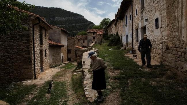 Sinforosa Sancho, 84, dan suaminya Juan Martin Colomer, 84, berjalan di sepanjang jalanan utama Desa La Estrella. Desa itu pernah dihuni lebih dari 200-an orang.