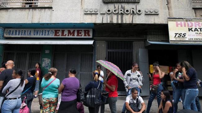 Warga Venezuela mengantri di depan mesin ATM. Negara ini telah kehilangan nilai mata uangnya lebih dari 99 persen. (REUTERS/Adriana Loureiro)