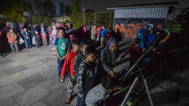 Sejumlah anak antre untuk mengamati gerhana bulan total dengan menggunakan teleskop di Lapangan Salman ITB, Bandung, Jawa Barat. (Antara/Raisan Al Farisi)