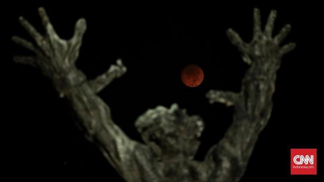 Fase gerhana bulan total 'Micro Blood Moon' dari Monumen Pembebasan Irian Barat, Jakarta. Januari lalu, terjadi fenomena 'Blood Moon'. Terdapat perbedaan di antara keduanya. (CNN Indonesia/Bisma Septalisma)