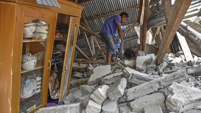 Warga mencari perlengkapan wisatawan asal Malaysia yang tewas tertimpa rumah roboh akibat gempa, di Desa Sajang, Kecamatan Sembalun, Selong, Lombok Timur, NTB, Minggu (29/7). (ANTARA FOTO/Ahmad Subaidi)