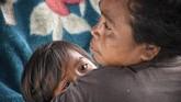 Seorang perempuan mengendong anaknya di tenda perawatan pascagempa di Desa Sembalun Bumbung, Kecamatan Sembalun, Selong, Lombok Timur, NTB, Minggu (29/7). (ANTARA FOTO/Ahmad Subaidi)