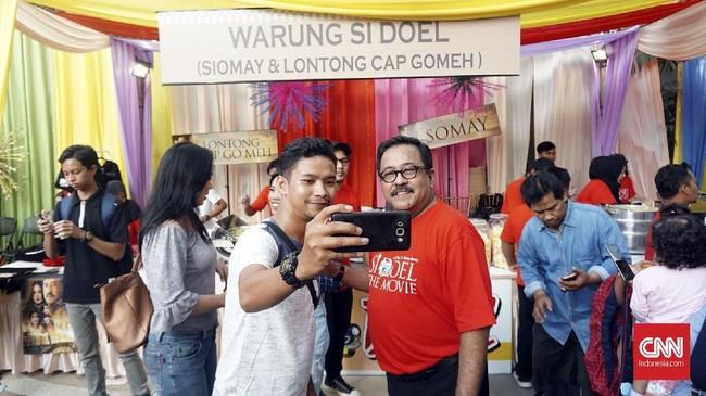 Rano Karno selakusutradaraSi Doel The Movie mengatakan bahwa ia memang ingin membuat gala premier ini seperti berada di pasar rakyat, kala tamu dan masyarakat datang menonton sambil jajan makan-makanan tradisional. (CNN Indonesia/Agniya Khoiri)