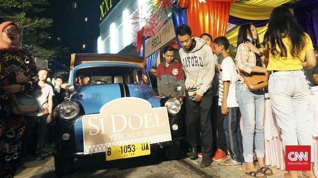 Datang menggunakan oplet tua, para pemain 'Si Doel The Movie' datang menyapa sekaligus tampil bersama menyanyikan lagu tema 'Si Doel Anak Betawi'. (CNN Indonesia/Agniya Khoiri)