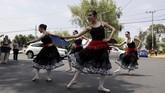 Perusahaan itu 'menurunkan' balerina-balerina yang menari berjajar dengan rok tutu dan pointe shoe. Dagu mereka terangkat tinggi, lengan mereka meliuk gemulai. Di hadapan para pengguna kendaraan, mereka beraksi. (REUTERS/Henry Romero)