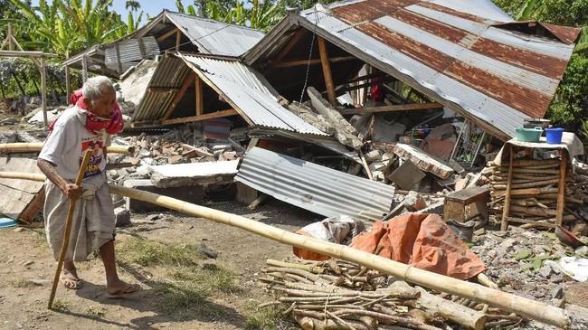 Warga berjalan di depan rumah yang roboh akibat gempa di Desa Sajang, Kecamatan Sembalun, Selong, Lombok Timur, NTB, Minggu (29/7). (ANTARA FOTO/Ahmad Subaidi)