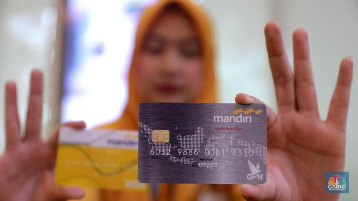 Nasabah menukar kartu ATM visa menjadi GPN Plaza Mandiri, Jakarta, Senin (30/7). Bank Indonesia (BI) dan perbankan menggelar kampanye Gerbang Pembayaran Nasional (GPN). Kegiatan penukaran kartu pada 30 Juli-3 Agustus 2018. Pekan penukaran kartu berlogo GPN merupakan tindak lanjut acara peluncuran bersama kartu berlogo GPN di Jakarta pada 3 Mei 2018. Kartu berlogo GPN diharapkan untuk memudahkan masyarakat untuk melakukan transaksi pada seluruh kanal pembayaran (EDC) yang tersedia, sehingga akan meningkatkan efisiensi waktu dan biaya. (CNBC Indonesia/Muhammad Sabki)