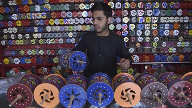 Bisnis itu pun telah turun-temurun. Anak-anak remaja yang orang tuanya merupakan penjual layang-layang pun sudah akrab dengan produksi itu. (AFP PHOTO / WAKIL KOHSAR)