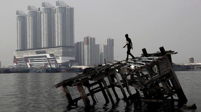 Seorang pemuda berjalan di atas reruntuhan perahu kayu sementara di kejauhan asap kabut menutupi area Jakarta Utara, Indonesia. (REUTERS/Beawiharta)