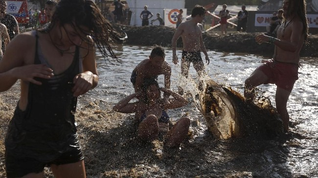 Ini karena di festival tersebut para pengunjung bisa bermain lumpur dan tanah, bahkan ada ajang gulat lumpur di sana. (REUTERS/Kacper Pempel)