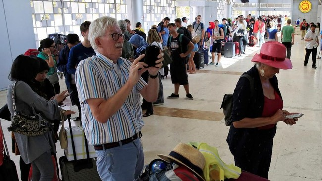 Turis asing memerhatikan ponsel saat menunggu dapat masuk ke dalam bandara internasional Lombok, Senin (6/8). (REUTERS/Beawiharta)