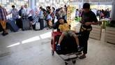 Seorang anak yang kelelahan beristirahat di atas koper yang ditumpuk di troli. Kepanikan, terutama di kalangan turis, terjadi setelah gempa berkekuatan 7 SR yang mengguncangkan kepulauan Lombok, NTB. (REUTERS/Beawiharta)