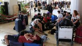 Rombongan turis asing beristirahat di lantai bandara internasional Lombok menunggu mendapatkan penerbangan yang akan membawa mereka terbang dari salah satu destinasi favorit pariwisata Indonesia.(REUTERS/Beawiharta)