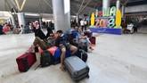 Rombongan turis beristirahat menunggu mendapatkan penerbangan di Bandara Internasional Lombok, Selasa (6/8). (AFP PHOTO / Adek BERRY)