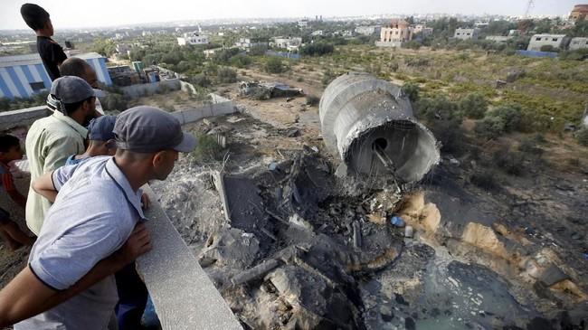 Warga Palestina memeriksa kerusakan akibat serangan Israel di Al-Mughraqa, pinggiran Kota Gaza. (REUTERS/Mohammed Salem)