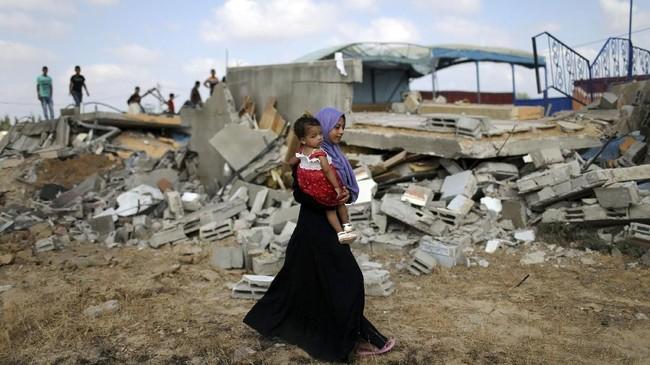 Seorang perempuan Palestina melintas di Khan Younis, pinggiran selatan Jalur Gaza. Serangan Israel disebut telah menewaskan seorang bayi berusia 18 bulan dan ibunya yang sedang hamil. (REUTERS/Ibraheem Abu Mustafa)