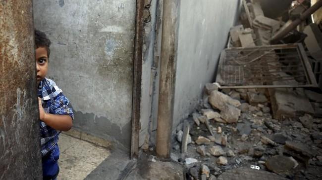 Seorang bocah Palestina melongok dari rumahnya yang rusak akibat serangan udara Israel di Al-Muqhraqa, pinggiran Kota Gaza. (REUTERS/Mohammed Salem)