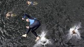 Seorang peserta kompetisi lompat tebing di dekat perkampungan Bohemian di Hrimezdiice, Rep. Ceko, meloncat ke air. (REUTERS/David W Cerny)