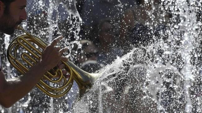 Anggota tim Gandini Juggling and Circa Tsuica tampil di antara air mancur di Somerset House ketika London didera cuaca panas di Inggris. (REUTERS/Toby Melville)