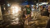 Seorang pria coba untuk menarik becak pada suatu jalanan yang banjir di kota Yangon. Hujan deras telah membuat daerah Mekong terkena dampak dengan Myanmar yang dilanda banjir parah yang memaksa 150 ribu orang mengungsi. (AFP PHOTO / YE AUNG THU)