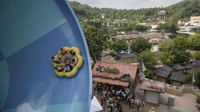 Orang-orang bermain di seluncur air di taman bermain Caribbean Bay di Yongin, di tepian kota Seoul. (AFP PHOTO / Ed JONES)