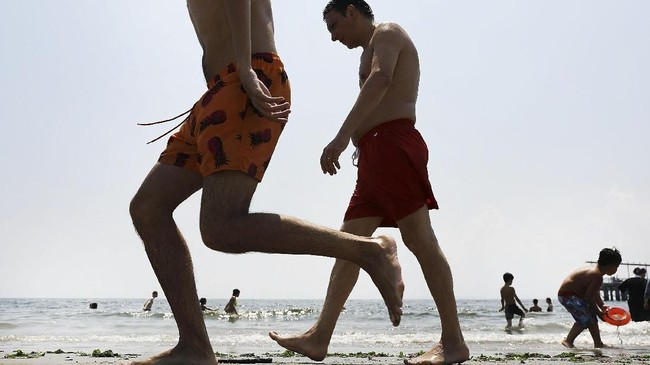 Pada musim panas, orang-orang berjalan di suatu pantai di Pulau Coney di New York. Saat itu New York mengalami gelombang panas sehingga penduduk kota berbondong-bondong mendatangi kolam renang dan pantai untuk mendinginkan badan. (Spencer Platt/Getty Images/AFP)