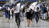 Para pejalan kaki di Tokyo, Jepang, yang hanya berlindung di bawah payung kesulitan menyebrang ketika hujan deras dan angin topan Shanshan terjadi. (REUTERS/Toru Hanai)