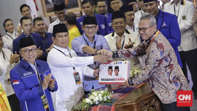 Prabowo dan Sandiaga menyerahkan dokumen secara simbolis kepada Ketua KPU Arief Budiman. Prabowo tampak mengenakan kemeja putih dengan peci hitam, sementara Sandiaga menggunakan kemeja biru dengan peci hitam. (CNN Indonesia/Adhi Wicaksono)