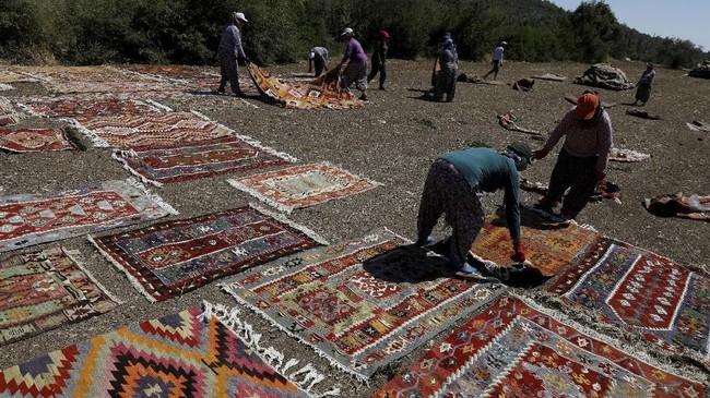 Para pekerja menjemur karpet tenunan tangan di tengah hari sementara mereka meneruskan proses pewarnaan, Jumat.