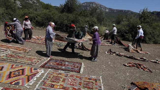 Selain warna-warnanya menjadi lembut setelah dijemur, proses tersebut juga memungkinkan para pekerja membersihkan karpet.