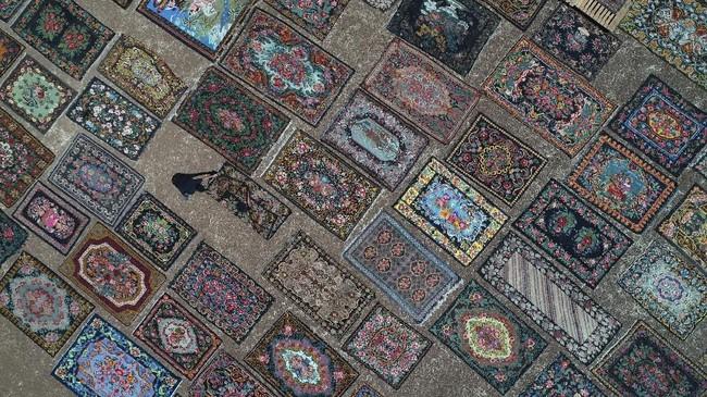 Seorang pria menjemur karpet di bawah teriknya matahari di Dosemealti, sebuah kota di tepi Laut Mediterania, Provinsi Antalya, Turki.
