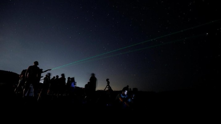 A man points a laser into the sky as people watch the Perseid meteor shower at Dwejra, outside the village of San Lawrenz on the island of Gozo, Malta August 12, 2018.  REUTERS/Darrin Zammit Lupi