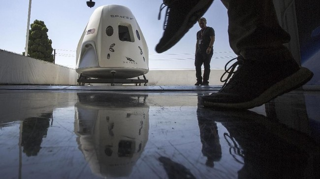 Pesawat ruang angkasaSpaceXDragon terlihat selama tur media di markas SpaceX dan pabrik roket di Hawthorne, California. (David McNew/Getty Images/AFP)