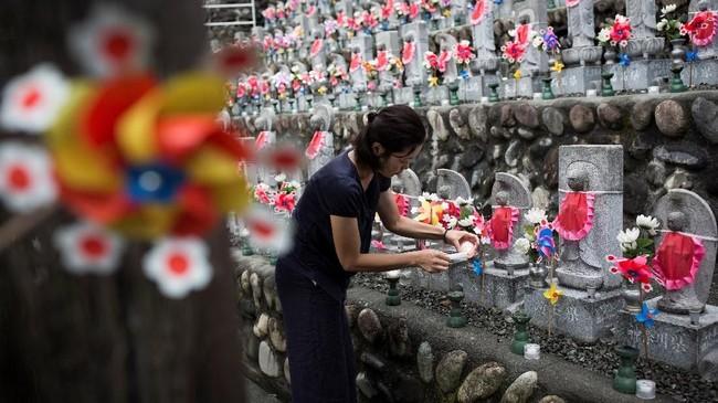 Para orang tua di Jepang melampiaskan kesedihan akan kehilangan anak pada kubur batu yang disebut jizo. (AFP PHOTO / Behrouz MEHRI)