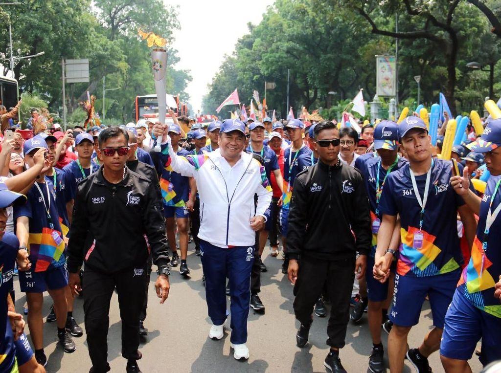 Utusan Khusus Presiden RI untuk Jepang Rachmat Gobel membawa obor saat prosesi Torch Relay Asian Games 2018 melintas di Jalan Merdeka Barat, Jakarta Pusat, Kamis (16/8). Istimewa.
