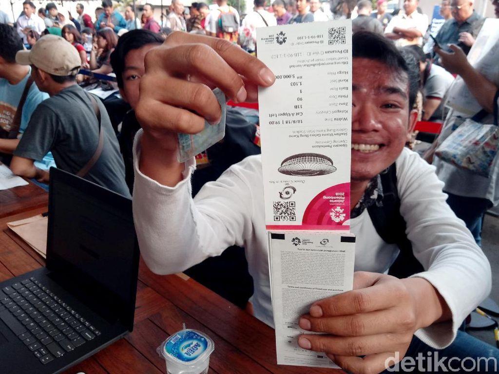 Senyum semringah salah satu pengunjung yang telah berhasil menukar tiket opening Asian Games 2018 usai mengantre panjang.