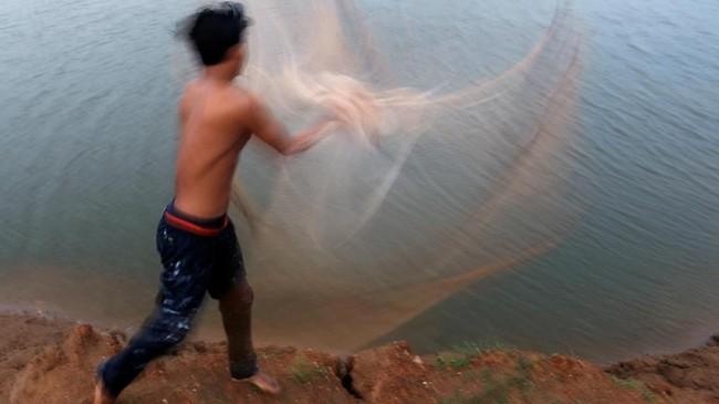 Seorang pria menebar jaring pada suatu danau di luar kota Phnom Penh, Kamboja. (REUTERS/Samrang Pring)