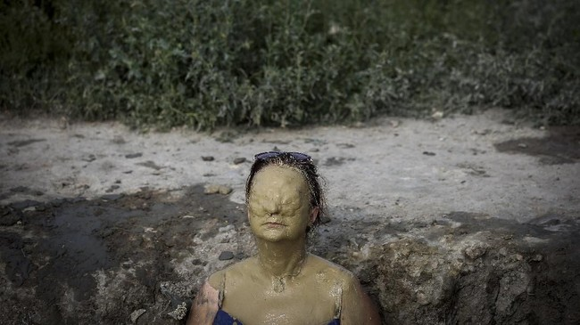 Seorang perempuan yang tubuhnya tertutupi lumpur menikmati sinar matahari di Ovca, dekat Beograd, untuk mendinginkan badan dari sengat gelombang panas. (AFP PHOTO / OLIVER BUNIC)