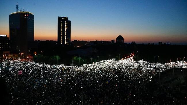 Para demonstran berkumpul ketika menggelar sebuah aksi protes di Bukarest, Romania. (Inquam Photos/Adriana Neagoe)