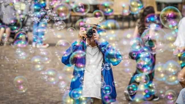 Seorang wisatawan mengambil foto gelembung-gelembung udara yang diciptakan oleh seorang seniman jalanan di Frankfurt, Jerman. (AFP PHOTO / dpa / Frank Rumpenhorst)