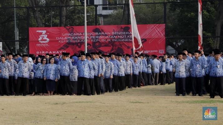 Pegawai PNS tiba menghadiri Upacara Kemerdekaan RI ke-73 di Lapangan Banteng, Jakarta, Jumat (17/8). Upacara diikuti pejabat Pemerintah Provinsi DKI Jakarta dan ratusan pegawai negeri sipil (PNS) DKI Jakarta yang berbaris memanjang dengan mengenakan batik Korpri biru dan celana hitam. Bagi peserta upacara pria mengenakan peci hitam. Tak ketinggalan pelajar, petugas pemadam kebakaran, anggota Kepolisian RI (Polri), Tentara Nasional Indonesia (TNI) baik itu angkatan darat, laut, dan udara ikut dalam barisan upacara.(CNBC Indonesia/Muhammad Sabki)