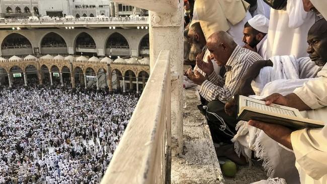 Jemaah calon haji tengah menyaksikan jemaah lainnya melakukan ziarah, mengelilingi Kakbah, dan berdoa di Masjid Agung, Mekah, Arab Saudi, Kamis (16/8). (REUTERS/Zohra Bensemra).