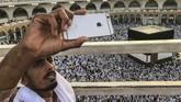 Seorang jemaah calon haji tengah berswafoto dengan latar jemaah calon haji lainnya tengah melingkari Kakbah dan berdoa di Masjid Agung, Mekah, Arab Saudi, Kamis (16/8). (REUTERS/Zohra Bensemra).