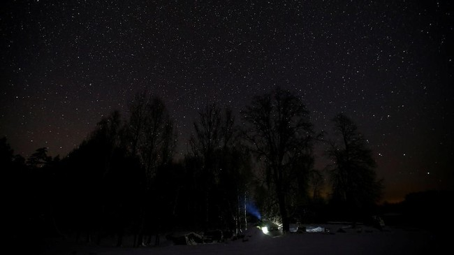 Pondok tempat Tamara dan Yuri Baikov yang terlihat di bawah bintang-bintang malam di hutan dekat desa Yukhovichi, Belarusia. (REUTERS/Vasily Fedosenko)