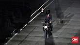 Presiden Joko Widodo mengendarai motor sambil melambaikan tangan saat menghadiri pembukaan Asian Games 2018 di Stadion Utama Gelora Bung Karno, Jakarta, Sabtu (18/8). (CNNIndonesia Adhi Wicaksono)