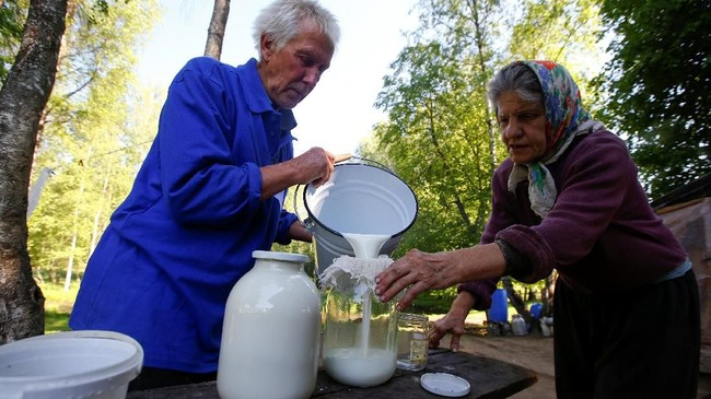 Tamara dan Yuri Baikov menuangkan susu kambing di pertanian kecil mereka. Suami dan istri ini telah hidup lebih dari seperempat abad dalam kehidupan primitif.(REUTERS/Vasily Fedosenko)
